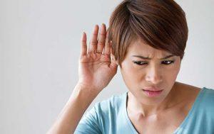 Frau mit Hand am Ohr