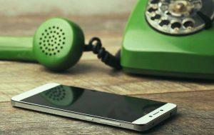 Altes grünes Telefon steht hinter einem liegendem Smartphone.