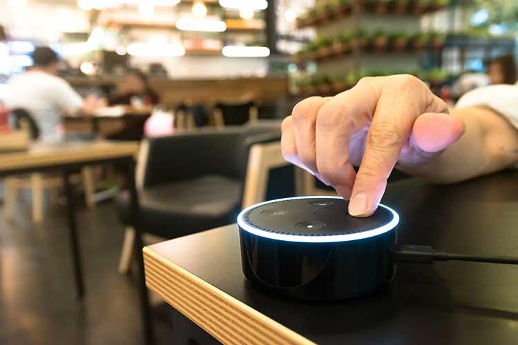 Nutzer drückt Knopf des Amazon Echo Dot.