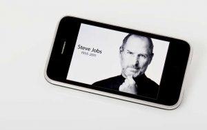 Gesicht und Name von Steve Jobs auf einem iPhone-Display anlässlich seines Todes