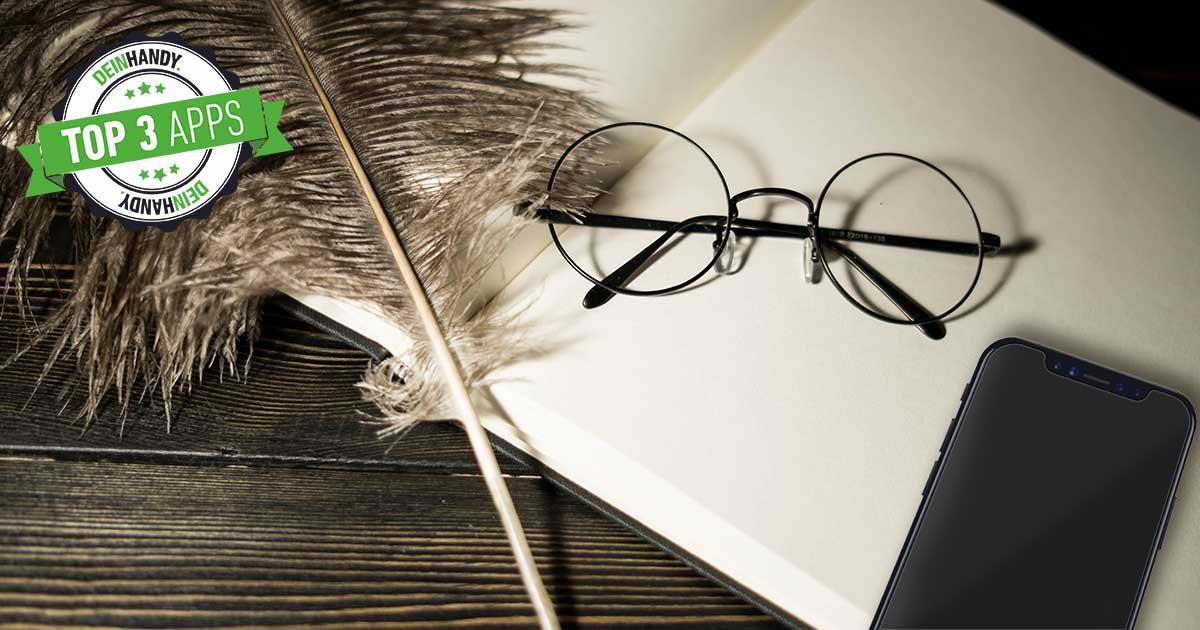 Harry-Potter-Apps: Auf einem Buch mit weißen Seiten liegen ein Smartphone, eine Schreibfeder und eine Brille mit runden Gläsern