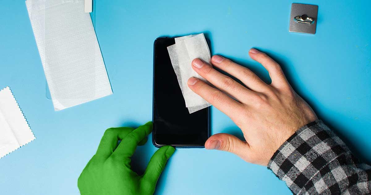 Handy reinigen: Smartphone liegt auf einem blauen Tisch und wird mit Papiertuch gesäubert