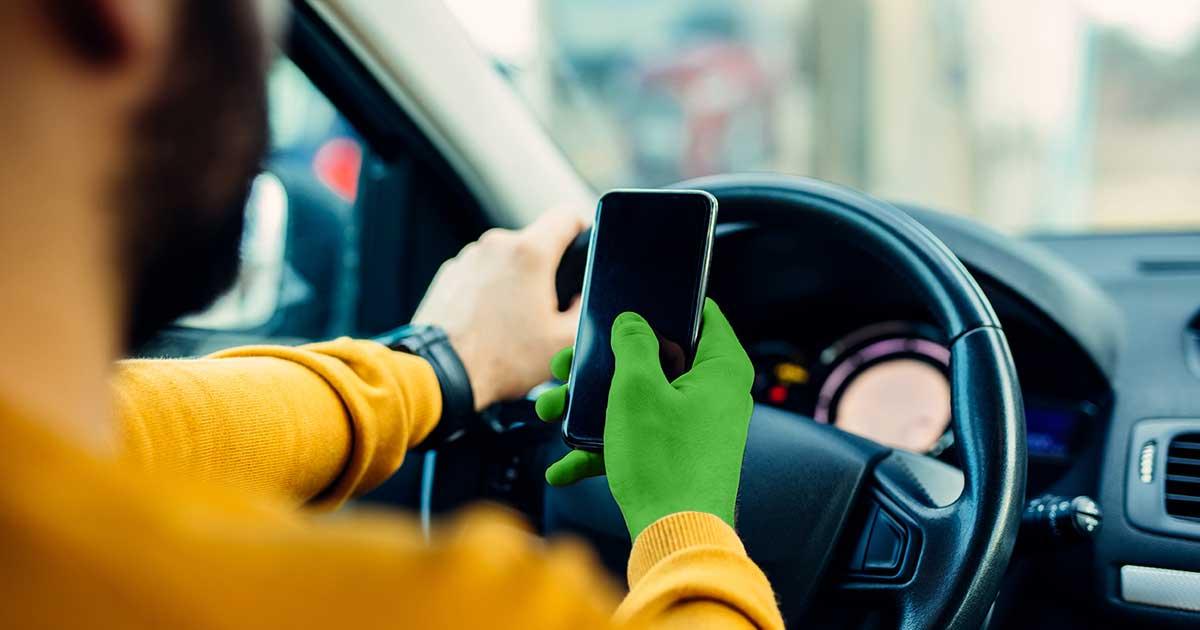 Handy am Steuer: Mann sitzt im Auto und hält ein Handy in der Hand