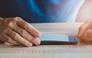 Handy reinigen: Schutzfolie wird auf Display aufgelegt