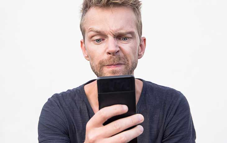 skeptical man with smartphone