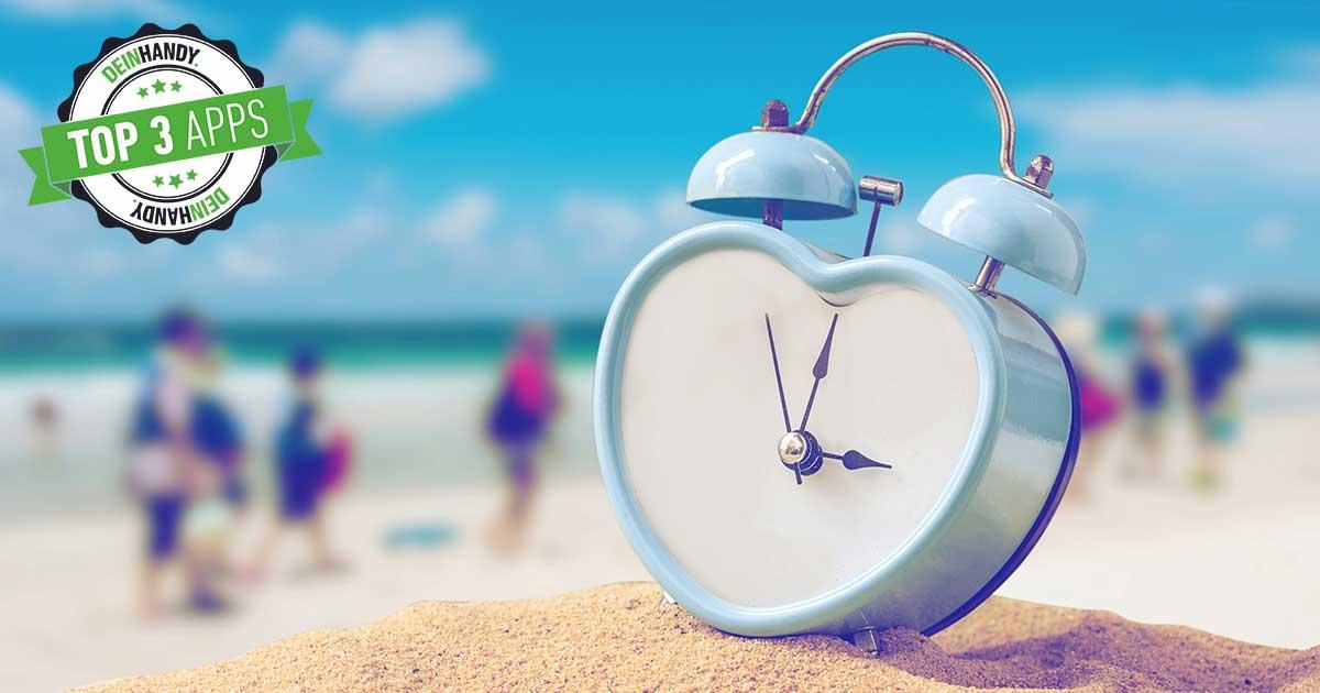 Urlaubscountdown: Herzförmige Uhr auf Sand, im Hintergrund Meer