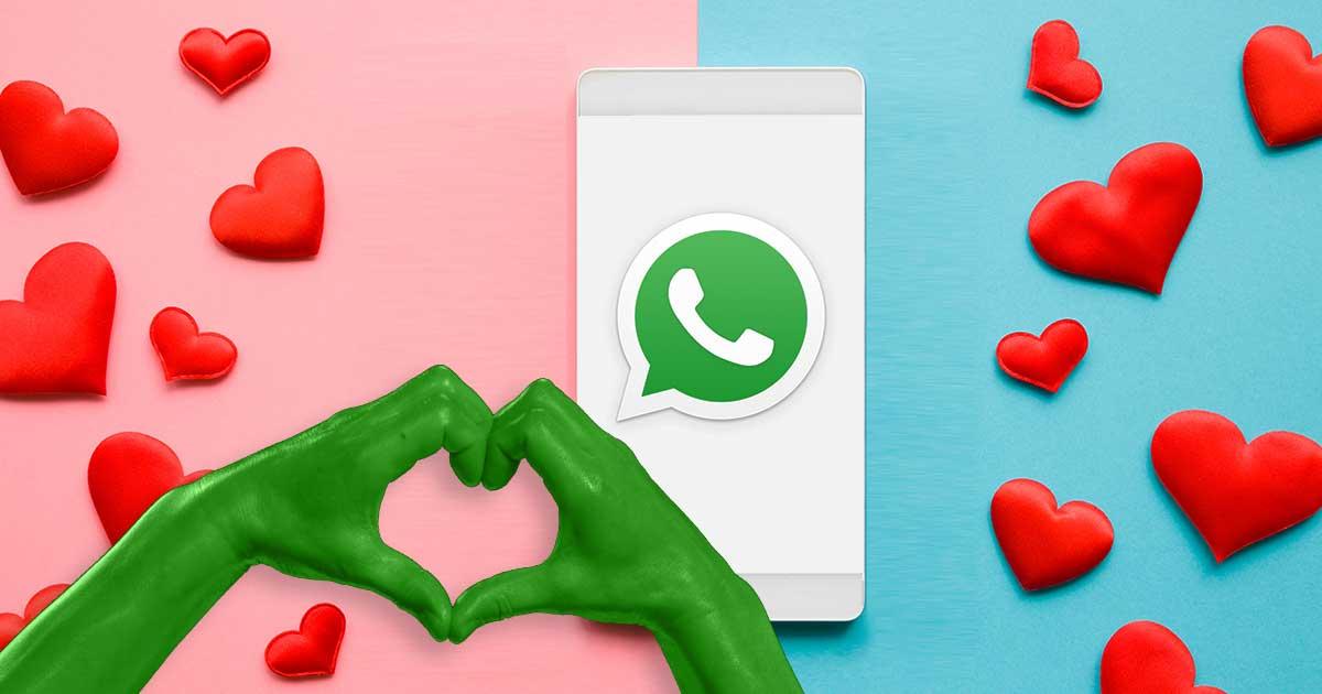WhatsApp-Sprüche zum Valentinstag: Handy mit WhatsApp Logo, Rosa-Blauer Hintergrund. Hände, die ein Herz formen
