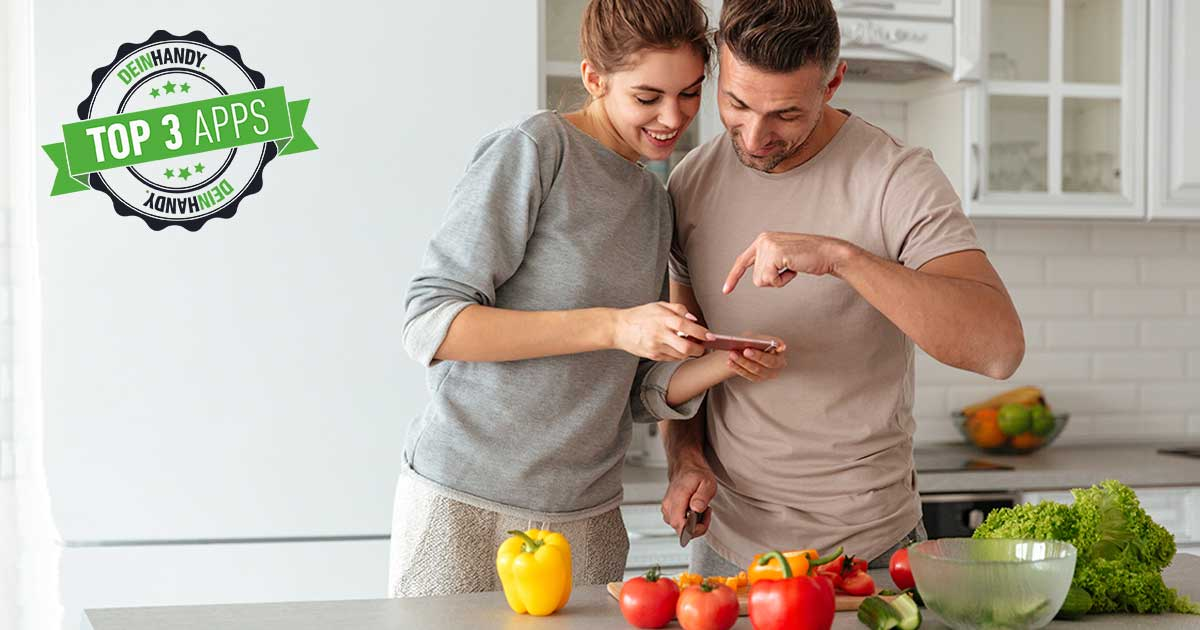 Rezepte-App: Paar, das kocht. Sie hält Handy in der Handy. Gemüse steht auf dem Tisch