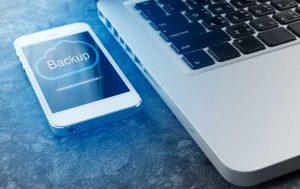 Handy einschicken: Handy während des Bachups neben einem Rechner
