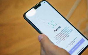 WhatsApp-Update: Hand mit iPhone, auf dem Bildschirm ist die Face-ID zu sehen