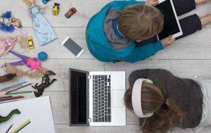 Apple-ID erstellen: Zwei Kinder, die auf dem Boden sitzen und mit Apple-Geräten spielen