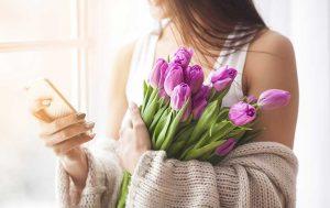 WhatsApp-Geburtstagsgrüße: Fraub mit Blumen und Smartphone