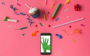 WhatsApp-Geburtstagsgrüße: Handy mit Deko vor pinkem Hintergrund
