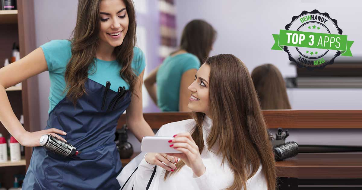 Frisuren-App: Zwei Frauen beim Friseur, die eine hält ein Smartphone in der Hand und zeigt etwas