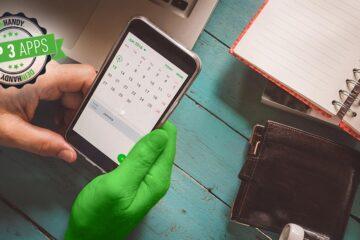 Kalender-App: Smartphone in der Hand, Tisch im Hintergrund