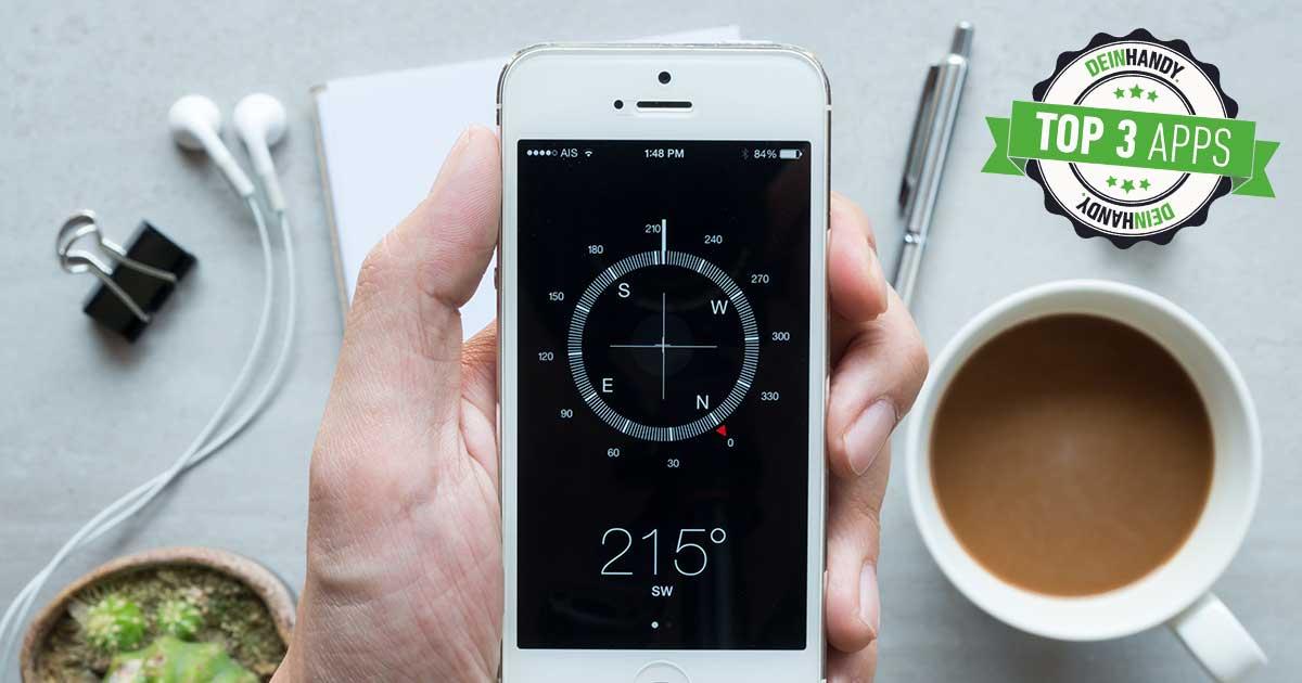 Kompass-App: Handy mit Kompass über einem Tisch mit Kaffeetasse