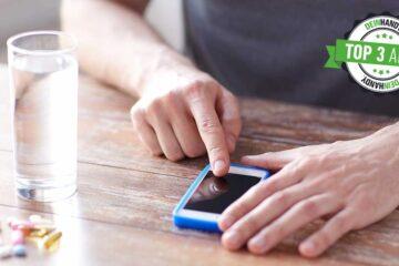 Medikamenten-App: Handy mit Pillen auf einem Tisch