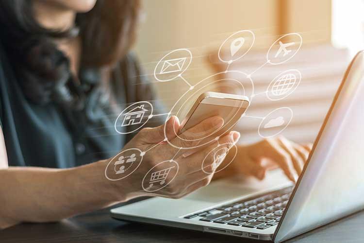 Ein Nutzer bedient Laptop und Smartphone parallel..