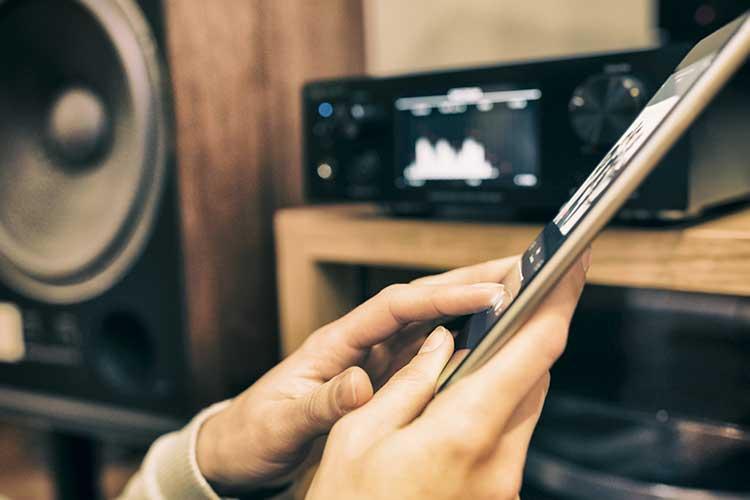 Smartphone mit Musikanlage im Hintergrund.
