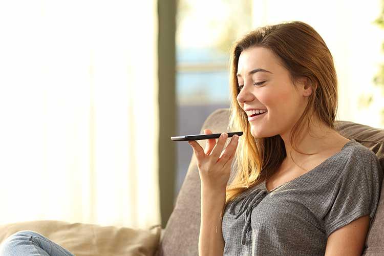 Frau nutzt Sprachsteuerung per Smartphone.