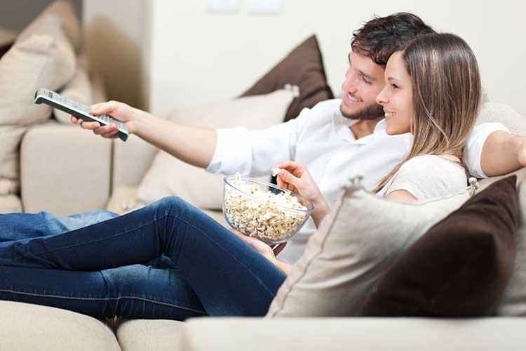 DSL Geschwindigkeit: junges Paar sitzt mit Popcorn auf dem Sofa vor dem Fernseher