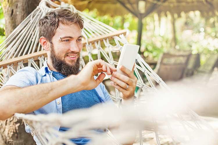 Gardena smart system: Mann liegt mit Handy in der Hand in einer Hängematte