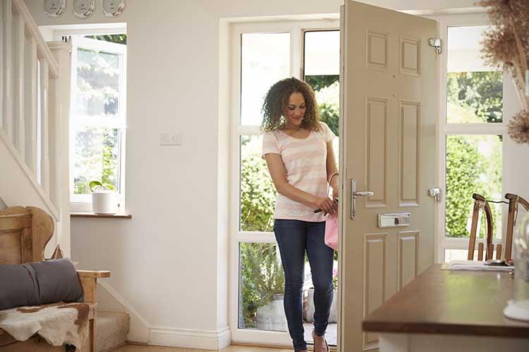 IFTTT: junge Frau kommt nach Hause und öffnet die Tür