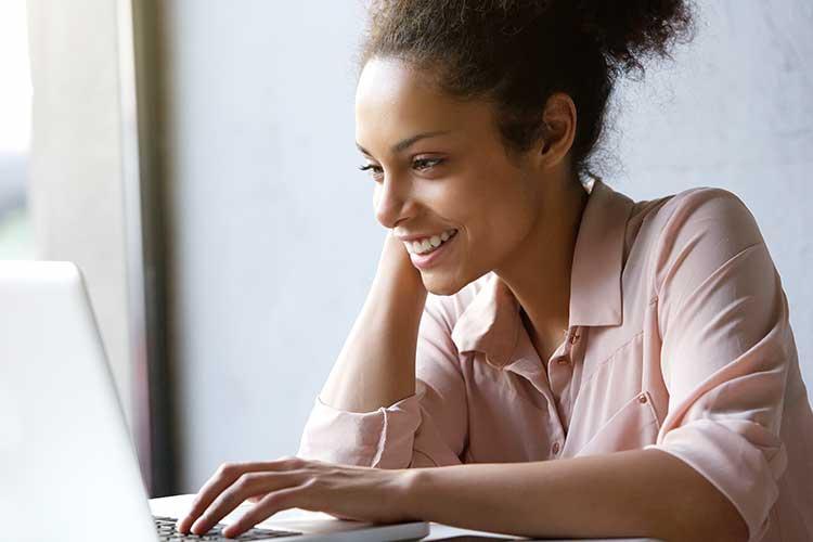 DSL Geschwindigkeit: lächelnde Frau sitzt vor geöffnetem Laptop