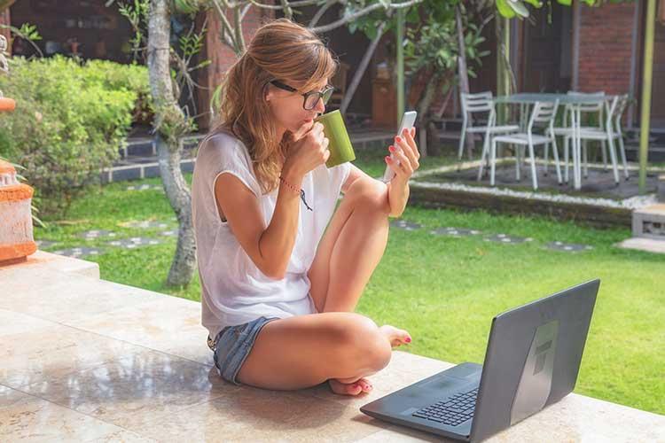 gardena smart system: Frau trinkt Kaffee und schaut auf ihr Handy
