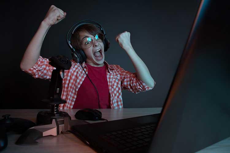 DSL Geschwindigkeit: junger Mann mit Brille sitzt im dunkeln vor dem Computer und freut sich