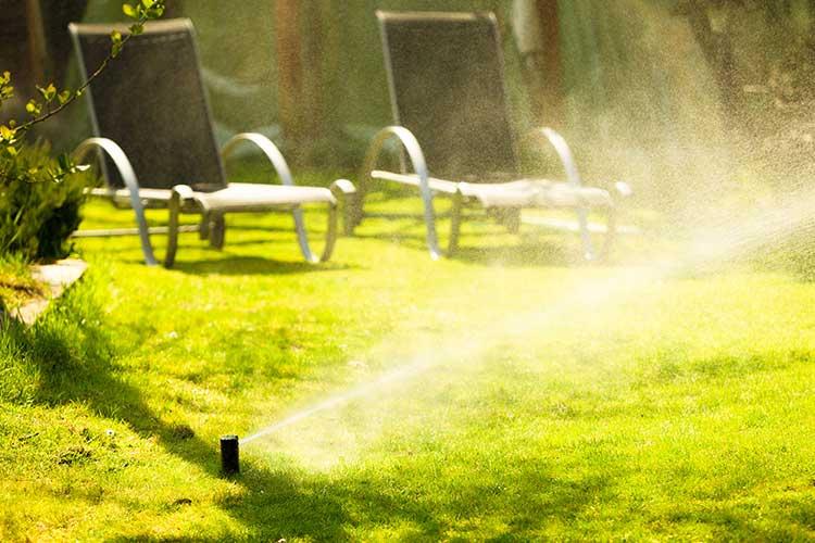 Gardena smart system: Rasensprenger gießt grünes Gras, Liegestühle im Hintergrund