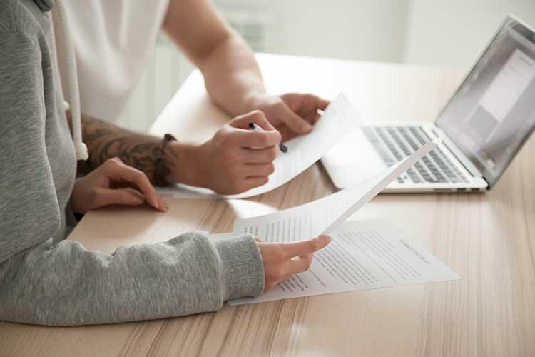 DSL Vertrag: zwei Menschen sitzen mit Laptop und bedrucktem Papier am Tisch
