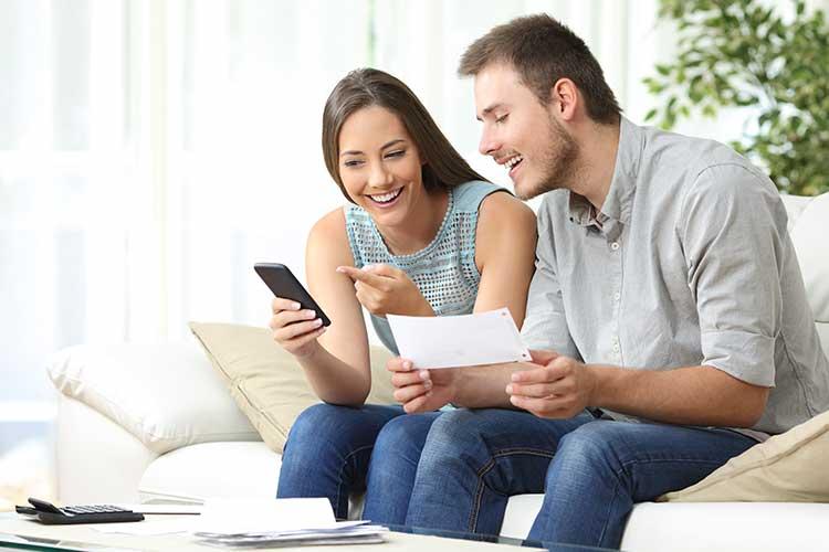 Smart Home Versicherungen: Mann und Frau sitzen lächelnd auf dem Sofa