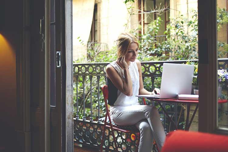 Frau sitzt auf dem Balkon und arbeitet mit dem Laptop per WLAN.