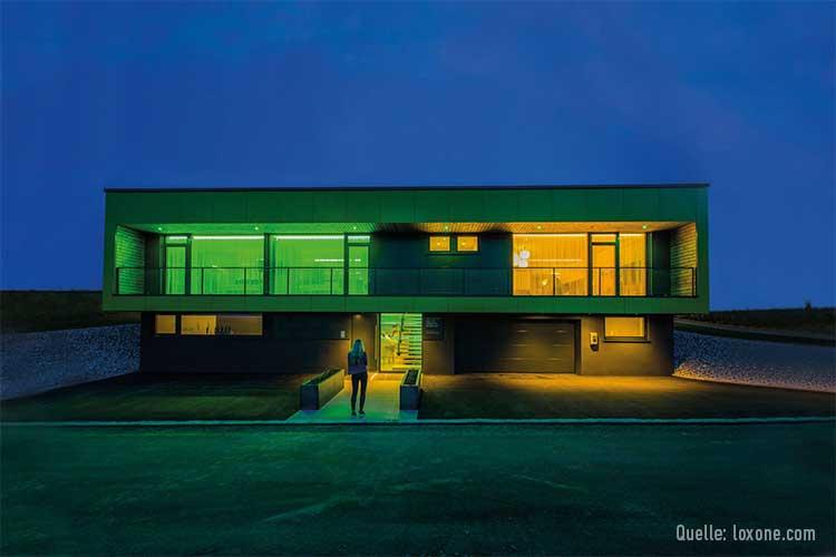 Das Musterhaus von Loxone: junge Frau steht im Dunkeln vor hell erleuchtetem Haus