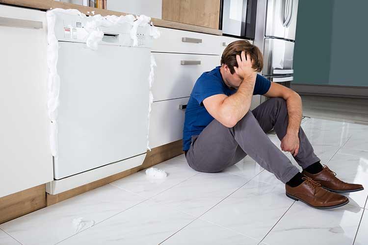 Mann sitzt verzweifelt vor defekter Spülmaschine.