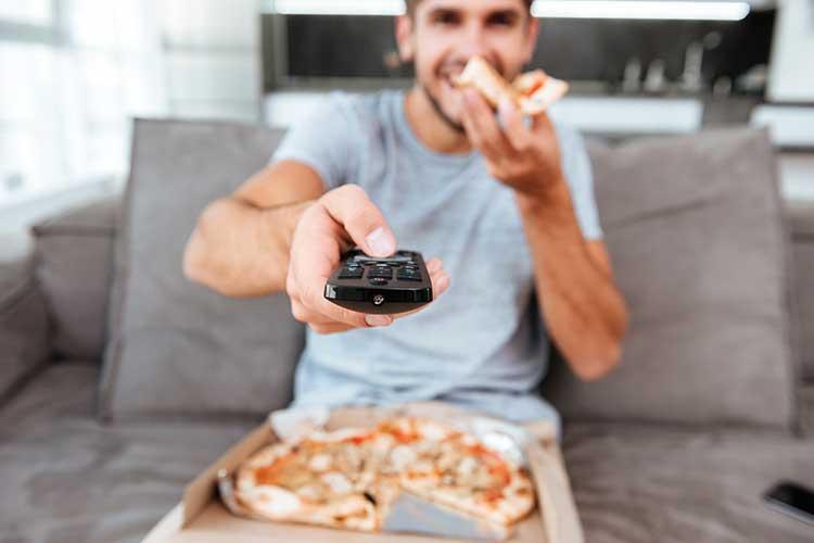 Mann sitzt mit Pizza und Fernbedienung auf dem Sofa: Löst die Sprachsteuerung herkömmliche Bedienelemente ab?
