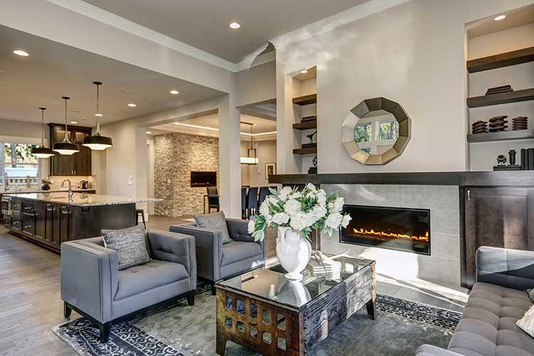 SmartThings: Modernes Wohnzimmer mit Sesseln und Kamin im Vordergrund, hinten ist eine beleuchtete Küche zu sehen