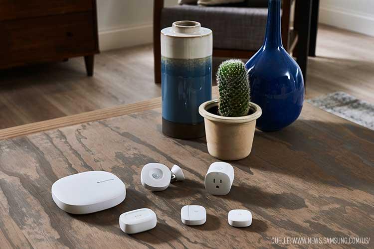 SmartThins Produkte: Hub, intelligente Sensoren und Steckdosen liegen nebeneinander auf dem Tisch