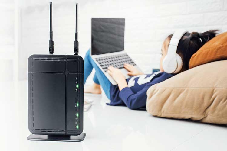 Mädchen im Hintergrund liegt mit Laptop und Kopfhörern auf dem Bett, im Vordergrund ist ein Router zu sehen
