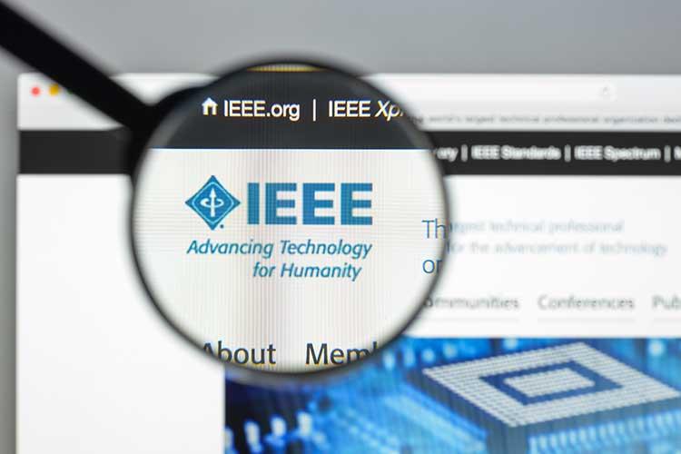 IEEE 802.15.4: Blaues Logo des IEEE auf der Homepage des Instituts durch ein Vergrößerungsglas