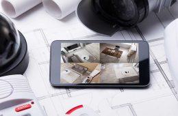 Sicherheitssysteme Smart Home_Handy mit Überwachungsbildern liegt zwischen Kamera, Alarmanlage und anderen smarten Produkten