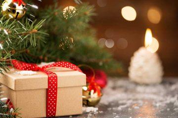 Ein verpacktes Geschenk mit roter Schleife liegt zu Weihnachten unter dem Baum