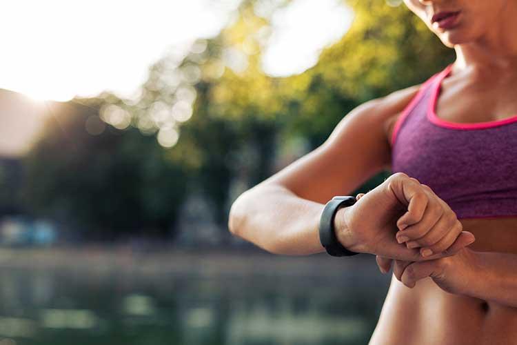 Weihnachten: Junge Frau schaut beim Joggen auf ihre Fitness-Uhr