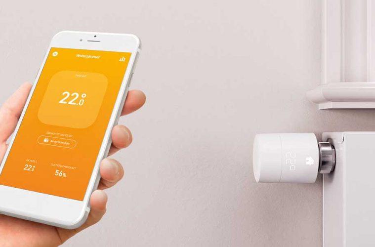Tado Heizkörperthermostat installieren - Handy mit Smartphone und Tado App, im Hintergrund eine Heizung mit Thermostat