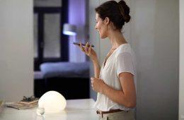 Alexa und Philips Hue verbinden: Frau, die ein Handy in der Handy hält. Licht im Hintergrund