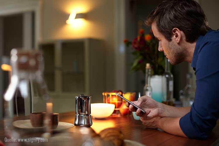 Alexa und Philips Hue verbinden: Mann mit Smartphone in der Küche, Licht im Hintergrund