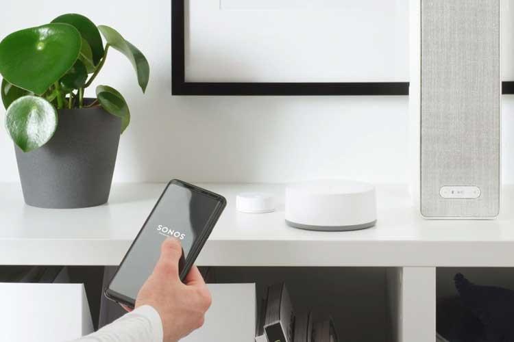 IKEA Symfonisk via Sprachbefehl steuern: Hand mit Handy und Sonos App, im Hintergrund ein Symfonisk Lautsprecher